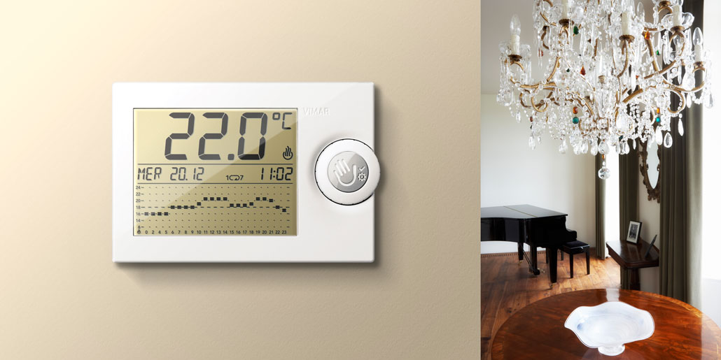 Vimar thermostat with mechanical levers for simplified programming and large LCD display for maximum readability with push wheel user interaction design by quickpartners+ in closed state in classic room