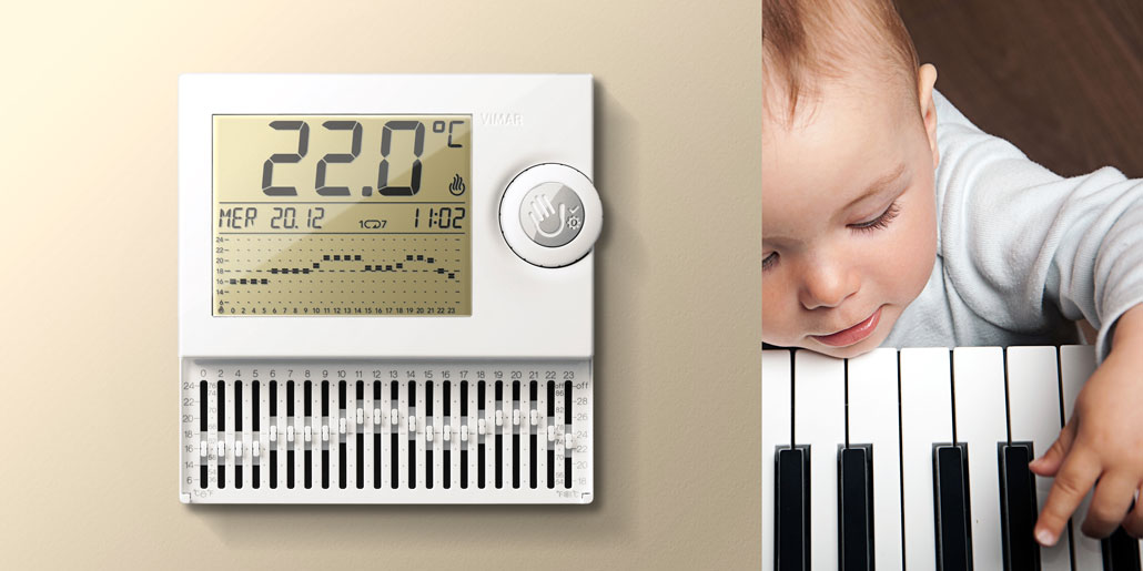 Vimar thermostat with mechanical levers for simplified programming and large LCD display for maximum readability with push wheel user interaction design by quickpartners+ in open state with piano playing child