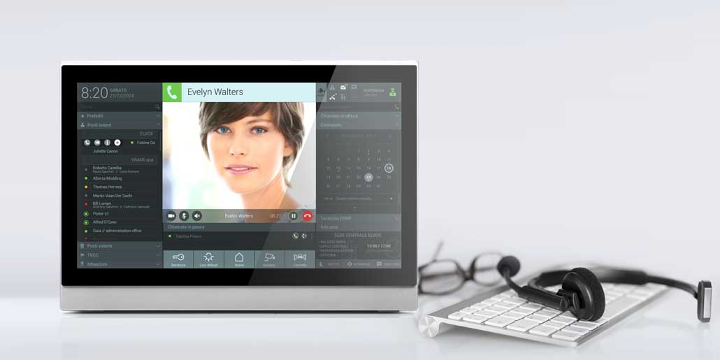 Vimar Elvox Ip-based Porter Center with access control, videocall center, building surveillance and energy monitoring graphic icon and usability design quickpartners LCD screen with keyboard and headset on white desk