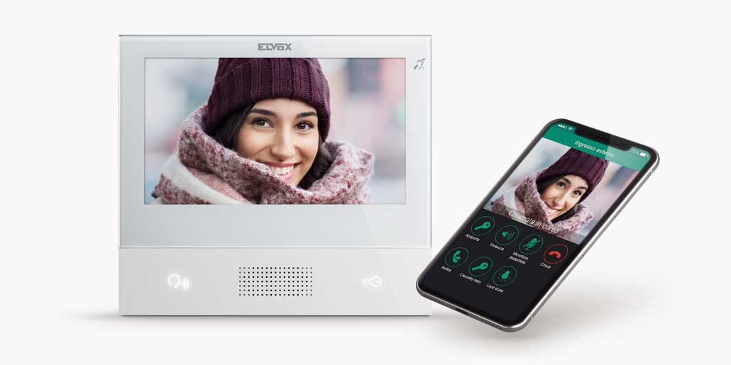 Vimar Elvox Tab 7 video door phone flat and slim design with touch display and remote App design quickpartners with young woman calling on iphone x an white background